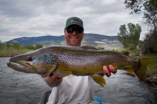 Happy angler with a giant brown trout