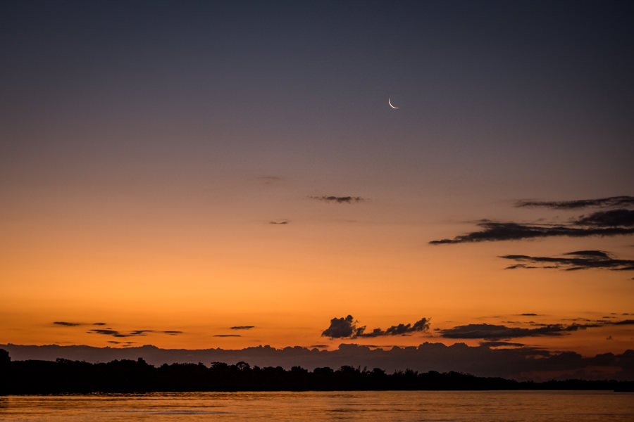 Last light and a crescent moon on Rio Parana