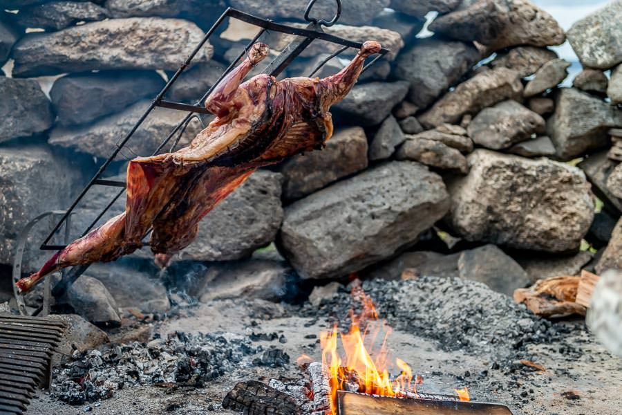 """... She was preparing for lamb asado. For this method of cooking a whole lamb is prepared and placed on a specially designed steel cross that allows you to adjust the angle of the lamb,  moving it closer or further away from the wood fire as needed. """