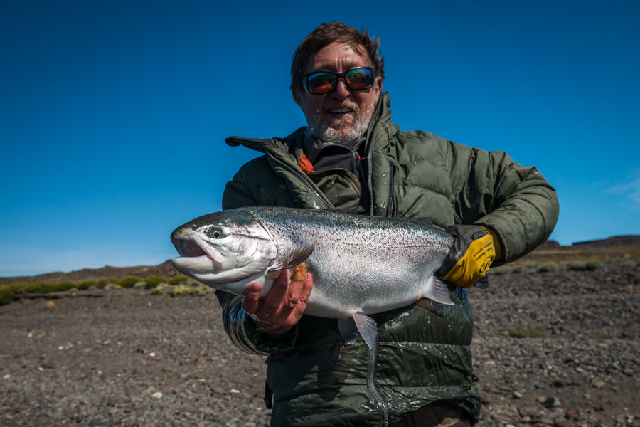 "My fishing partner for the week, Roberto from Buenos Aires, with a ""chromer"" from Cochinos Bay. The alkaline nutrients of the lake produce a chrome bright color to the lake rainbows"
